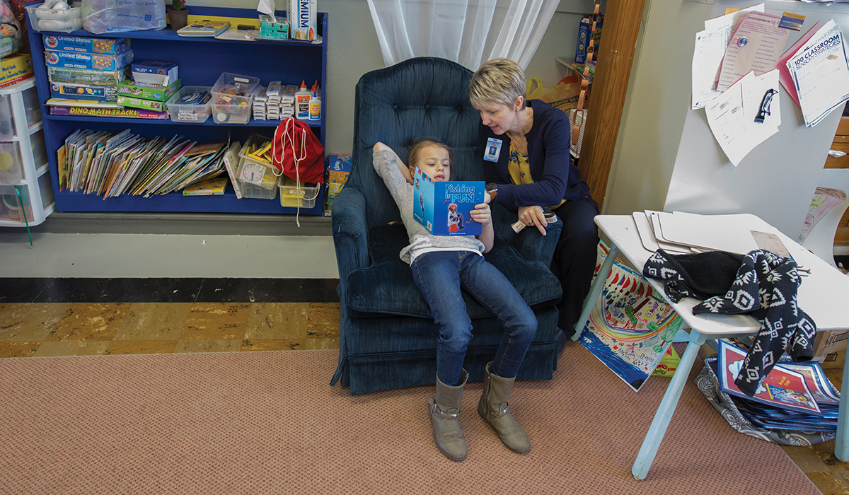 Principal Stacey Green works with kindergarten student, Paisley Shamburg with reading at the Stockton Elementary School.