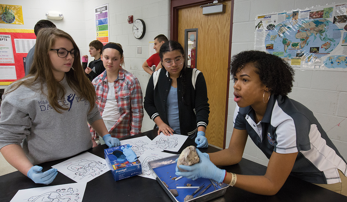 Makeena Barnt, Ava Mason and Joshlyn Rodriguez watch Olathe North High School student Kaiya McKie demonstrate how a pig's heart works.