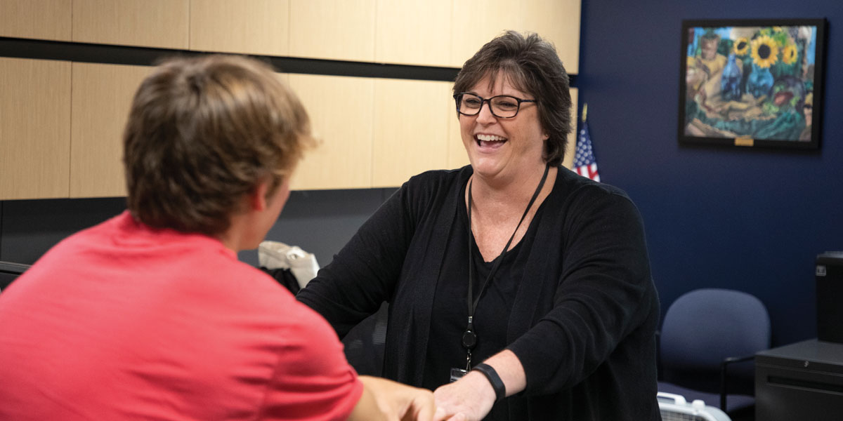 Judy Intfen greets a student as a counseling secretary at Mill Valley High.