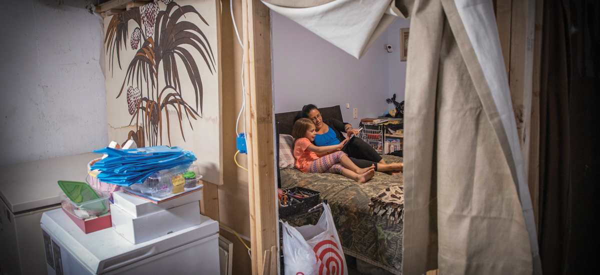 Veronica Stogsdill reads to her daughter Nessa in the family's makeshift bedroom.