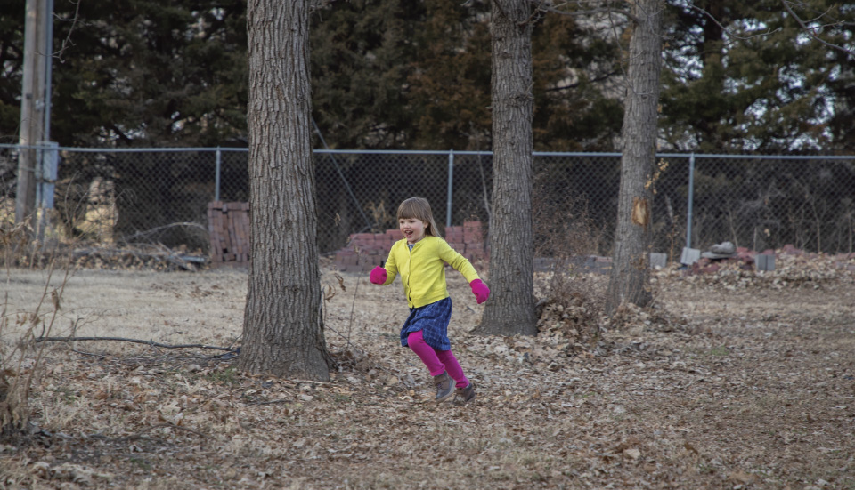 Child runs through tree-lined site of child care expansion