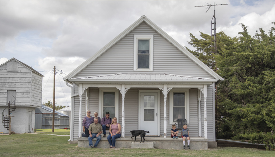 Mirla Coleman sits with her family members sit outside her parents ancestral home.